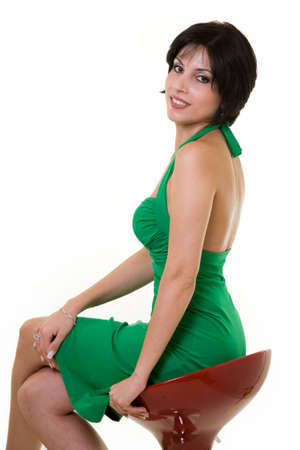 stool: Full body of a young Iranian woman wearing a green dress sitting on a red bar stool