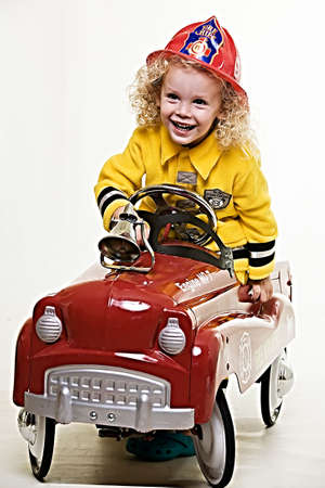 Portrait of an adorable little three year old boy wearing fireman costume sitting in a toy firetruck photo