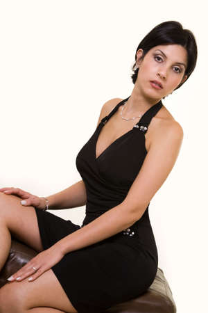 sit: Full body of a young Iranian woman wearing a black dress sitting on a brown foot stool