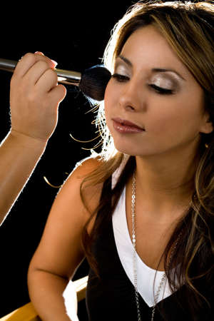 Close up of a beautiful brown hair Hispanic woman having her make up applied