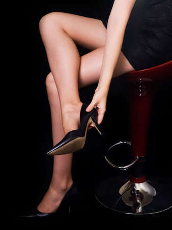 Womans bare legs in high heel shoes on black background Stock Photo