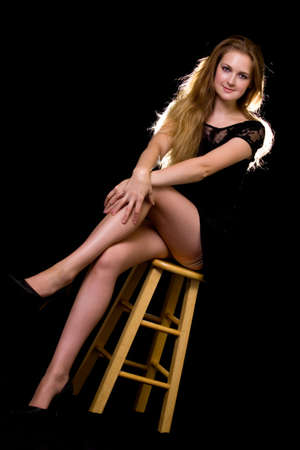Full body of a beautiful woman with long blond hair and sexy long thin legs wearing black dress sitting on a wooden stool on black background Stock Photo