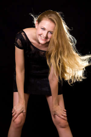 Beautiful woman with long blond hair blowing with happy expression leaning forward on black Stock Photo - 2005710