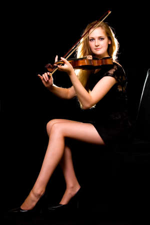 Full body of a beautiful woman with long blond hair and sexy long thin legs wearing black dress posing on black background playing a violin Reklamní fotografie