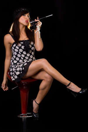 flapper: Full body of an attractive long haired brunette Hispanic woman wearing a black and white Flapper style dress and hat sitting on black while holding a long cigarette in a black holder Stock Photo