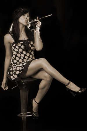 flapper: Todo el cuerpo de una atractiva morena de pelo largo mujer hispana que llevaba una en blanco y negro trampa estilo de vestimenta y sombrero sentado en negro en posesi�n de un largo cigarrillo negro en un titular