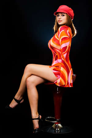 Full body of a beautiful woman with blond hair wearing bright colored seventies style dress and red hat sitting on stool on black background Stock Photo