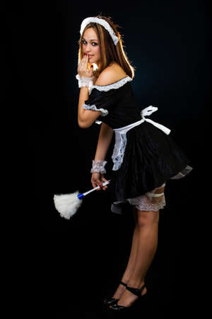 Full body of a beautiful woman with brown hair wearing a French Maid outfit and holding a white feather duster standing on black with hand over mouth