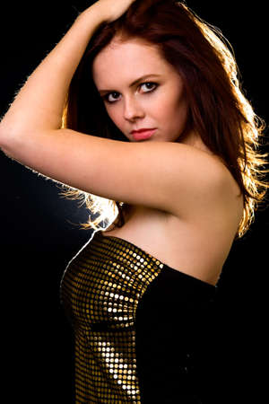 Attractive young brown hair woman standing sideways with hand over head with serious expression backlit over black