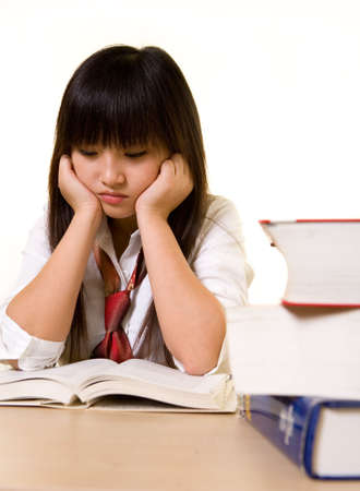 Young Chinese school girl wearing school uniform sitting in front of a pile of thick textbooks while reading one with a depressed expression on white photo