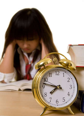 Young Chinese school girl wearing school uniform sitting in front of a pile of thick textbooks with hands on sides of head in a frustrated gesture with an alarm clock in front in focus photo