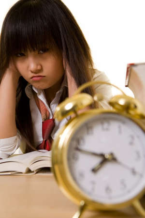 unifrom: Young Chinese girl wearing school uniform sitting in front of thick textbooks with hands on sides of head with a pouting face expression with an alarm clock in front