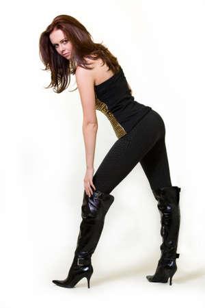 Full Körper einer schönen Frau, braune Haare trägt engen schwarzen Hosen und lange schwarze Stiefel Ferse hoch stehend