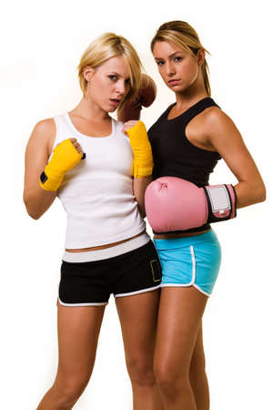 Portrait of two women wearing shorts and tank top one wearing pink boxing gloves and one wearing yellow hand wraps Stock Photo