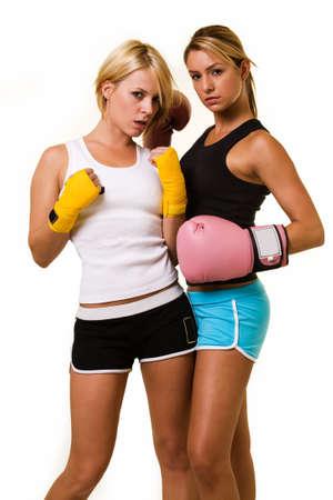 atletisch: Portret van twee vrouwen het dragen van korte broeken en tankcontainers boven het dragen van een roze bokshandschoenen en het dragen van een gele hand wraps
