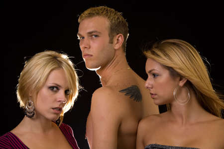 sexy blond: Portrait of a man in between two woman, one woman looking at the other to show jealousy