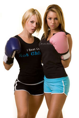 Portrait of two women wearing shorts and tshirts one wearing pink boxing gloves and one wearing blue photo