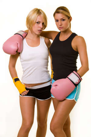 Portrait of two women wearing shorts and tank top one wearing pink boxing gloves and one wearing yellow hand wraps photo