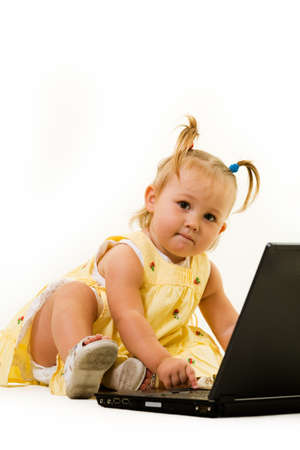 Adorable baby girl toddler in pigtails sitting on the floor working on a laptop computer Stock Photo - 2064963