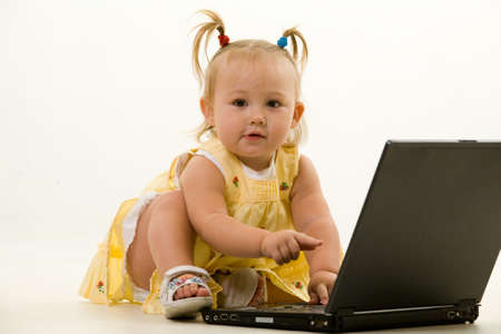 Adorable caucasian blond baby girl toddler in pigtails sitting on the floor working on a laptop computer Stock Photo - 2064964