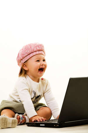 Adorable caucasian  girl toddler wearing a cute pink hat sitting on the floor working on a laptop computer laughing Stock Photo - 2064965