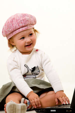 Adorable  girl toddler in cute pink hat on the floor with a laptop computer Stock Photo - 2073045