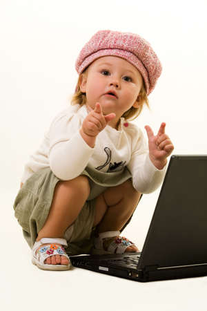 Adorable  girl toddler in cute pink hat on the floor with a laptop computer pointing fingers  Stock Photo - 2073034