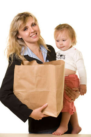 working mother: Attractive blond woman in business attire carrying a grocery bag in one arm and  in the other showing busy mother