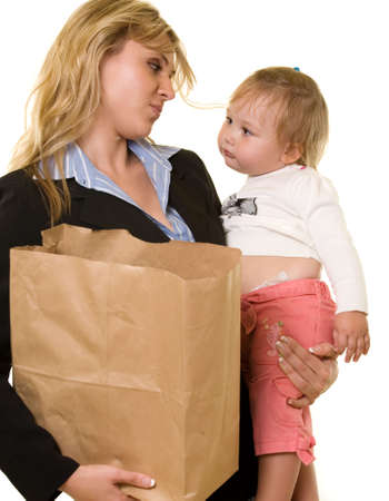 Attractive blond woman in business attire carrying a grocery bag in one arm and  in the other showing busy mother photo