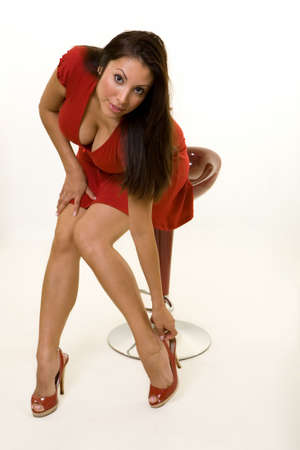 ankles sexy: woman wearing a red dress and matching shoes sitting on a red stool rubbing ankle Stock Photo