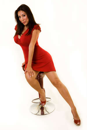 An attractive Hispanic woman wearing a red dress and matching shoes sitting on a red stool