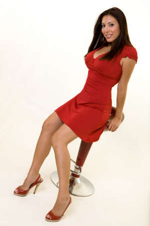 stool: An attractive Hispanic woman wearing a red dress and matching shoes sitting on a red stool