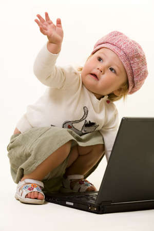 Adorable  girl toddler in cute pink hat on the floor with a laptop computer waving with one hand Stock Photo - 2094526