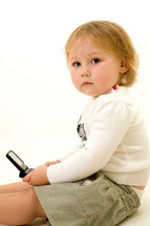 pager: Adorable  girl toddler sitting on the floor holding a text message pager