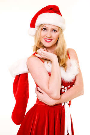 Attractive blond woman wearing sexy red and white Christmas dress and santa hat holding on to a stocking