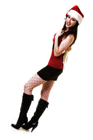 Full body of an attractive long haired brunette woman wearing sexy red and black top and short black skirt and santa hat and red fishnet stockings photo
