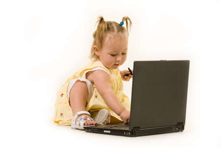 Adorable  girl toddler in pigtails sitting on the floor working on a laptop computer wearing a yellow dress Stock Photo - 2151333