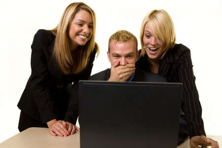 funy: Three office workers one man and two women all looking at a computer screen with laughing and shocked expressions
