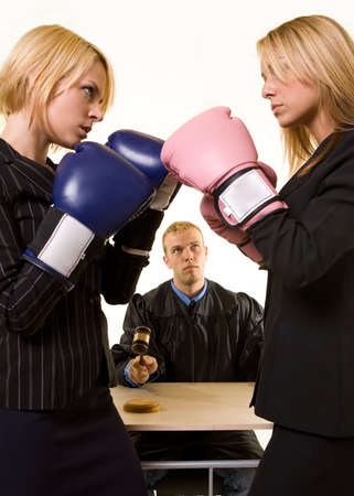 Two women lawyers wearing boxing gloves facing each other with a judge in background judge in focus
