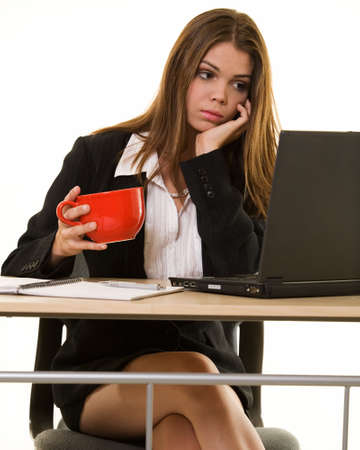 business attire teacher: Attractive young brunette woman in business suit looking bored while looking at a computer screen while holding a red coffee mug