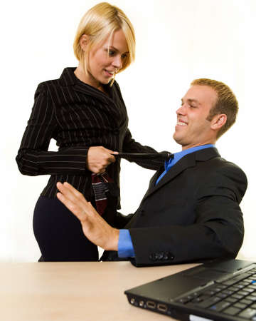 unethical: Business man sitting down with a business woman standing with a knee on his chair pulling on his tie