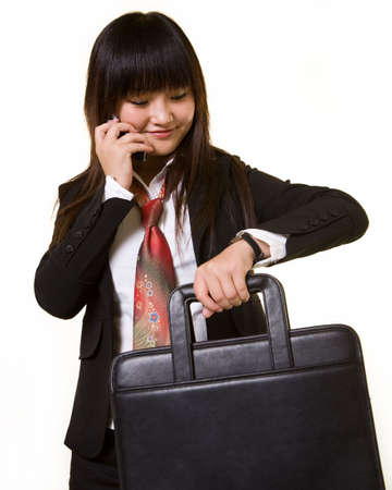 Attractive Chinese woman wearing a business attire holding a briefcase while talking on cell phone and checking wrist watch Stock Photo