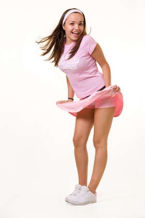 falda corta: Todo el cuerpo de una atractiva joven morena con el pelo corto en un traje rosa de tenis con el viento soplando hasta con falda feliz expresi�n emocionada