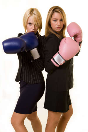 competitor: Portrait of two women wearing business attire and each wearing a pair of boxing gloves