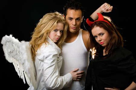 美しい金髪の天使とかなりブルネットの悪魔の女性の間に立っている魅力的な若い男性