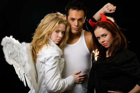 An attractive young man standing in between a beautiful blond angel and a pretty brunette devil woman