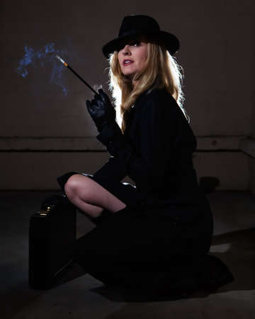Beautiful blond woman wearing a black trenchcoat and black fedora style hat in a dark alley smoking a cigarette photo