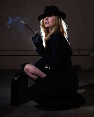 Mooie blonde vrouw draagt een zwarte trenchcoat en zwart stijl fedora hoed in een donker steegje het roken van een sigaret