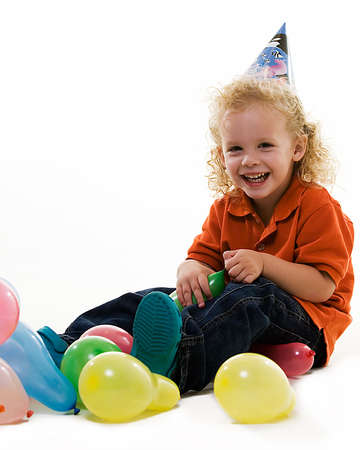 Adorable little three year old boy wearing party hat sitting with balloons with happy expression photo