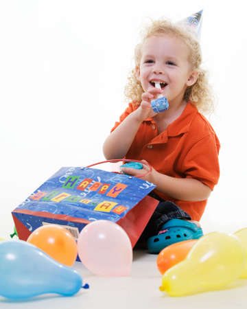 Adorable little three year old boy wearing party hat sitting with balloons with hand in a gift bag blowing on a party favor photo